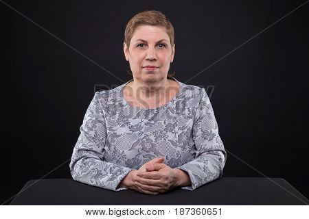 Portrait of sitting senior woman looking at camera on black background