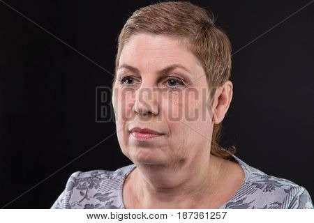 Portrait of sitting adult woman looking side on black background