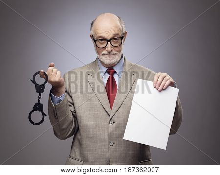 Senior business man with handcuffs and blank contract paper hints at danger of financial crimes