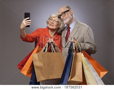 Happy couple taking selfie after shopping with many bags