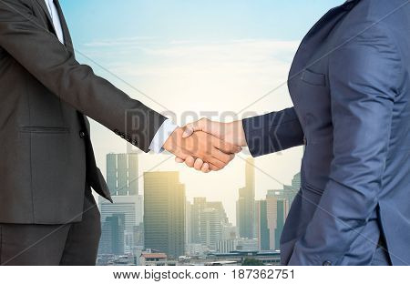 Double Exposure Of Handshake And Cityscape Background