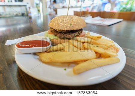 Delicious homemade recipe beef hamburger served with french fries ketchup and mayonaise on white plate on wood table