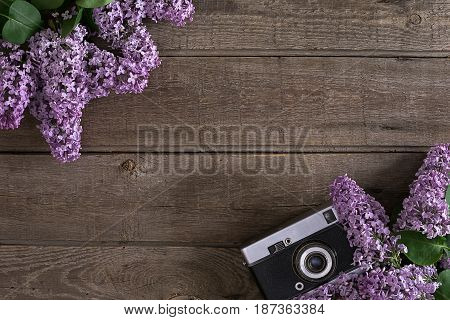 Lilac blossom on rustic wooden background with empty space for greeting message. Camera old. Top view. Mother's Day. Spring background concept.