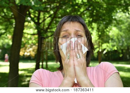 Woman with allergy symptom sneezing in a tissue