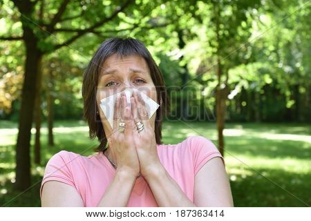 Woman with allergy symptom blowing her nose
