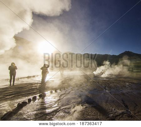 geyser field tatio with water surface at sunrise with sun shining in atacama desert, chile
