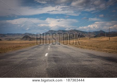 Road through a field of autumn grass on a background of high mountains Altai region, Siberia, Russia