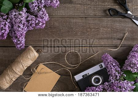 Lilac blossom on rustic wooden background with empty space for greeting message. Scissors, thread reel, small envelope and camera. Top view. Mother's Day. Spring background concept.