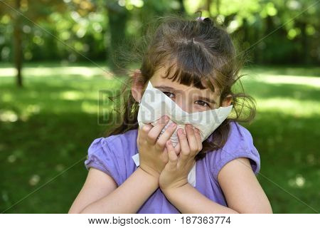 Young girl with allergy symptom sneezing in a tissue