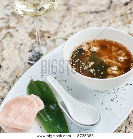 Crab soup served in white ceramic bowl with spoon, green leaf. pink crab chips and glass of white wine.