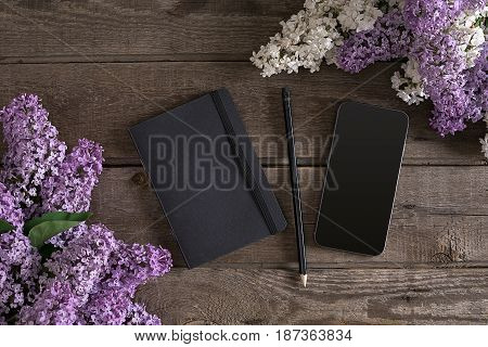 Lilac blossom on rustic wooden background with notebook for greeting message. Top view. Mother's Day. Spring background concept.