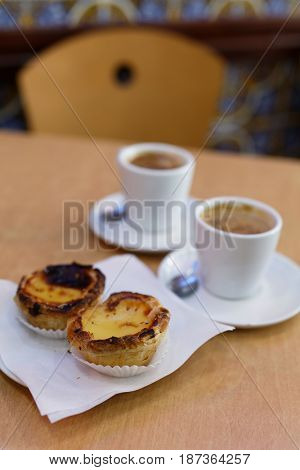 Portuguese egg tart pastry Pastel de nata on a plate with a cup of black coffee