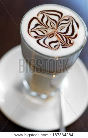Glass of coffee latte with floral pattern closeup