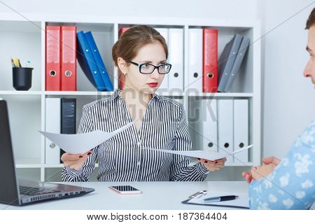 Angry male manager listening to emotional female boss holding documents pointing at papers. Dispute or argument concerning bad work documentation.