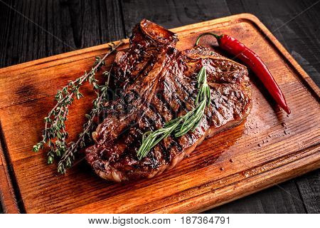Medium rare grilled steak on rustic cutting board with rosemary and spices , dark rustic wooden background, top view, place for text