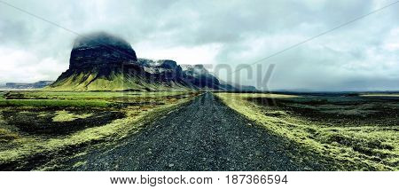 Barren black volcanic road cutting through green moss covered lava fields in Southern Iceland