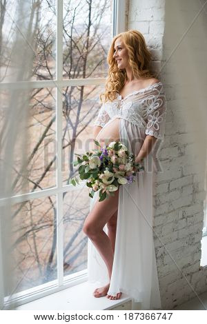 Charming pregnant girl looks out the window with a bouquet of flowers
