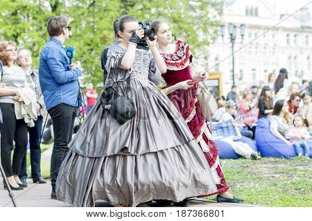 NIZHNY NOVGOROD, RUSSIA  May 20, 2017: Night of museums festival. Ladies hand-held digital techniques and gadgets, after performing at the main stage in costumes of the 19th century. NIZHNY NOVGOROD