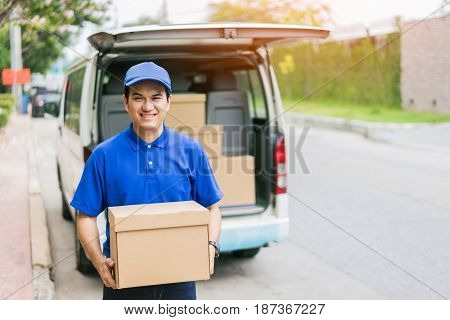 Delivery concept - Smiling happy young asian handsome man postal delivery courier man in back of cargo van delivering package holding box with service mind and blue uniform