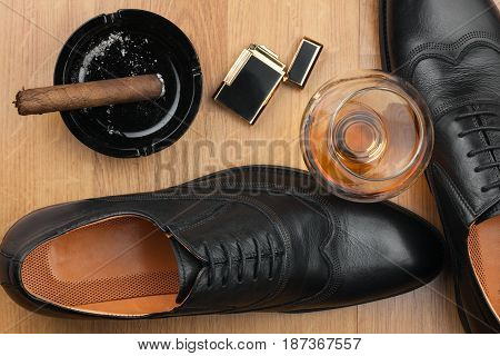Male lifestyle. Shoes cigar lighter and alcohol View from above
