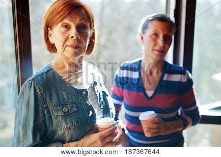 Aged female buddies wit hdrinks looking at camera