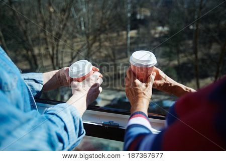 Hands of pensioners with hot drinks in open window