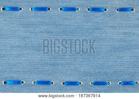 Frame made of blue ribbon inserted with denim fabric. View from above