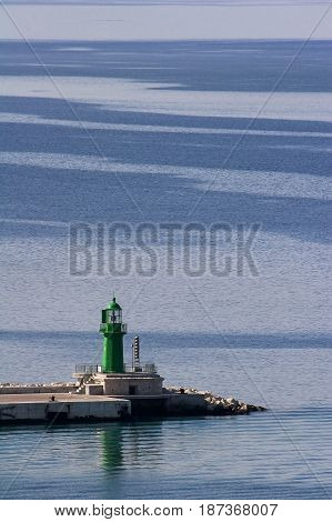 Lighthouse on breakwater in Split harbour, Green lighthouse on blue background