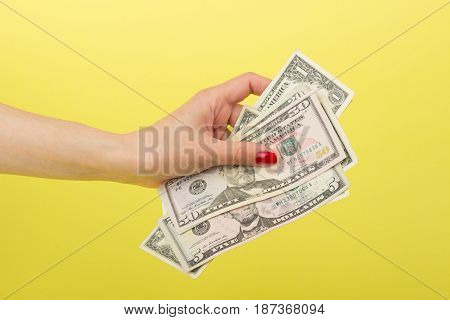 Fifty, Five And One Dollars In The Woman's Hand, Yellow Background