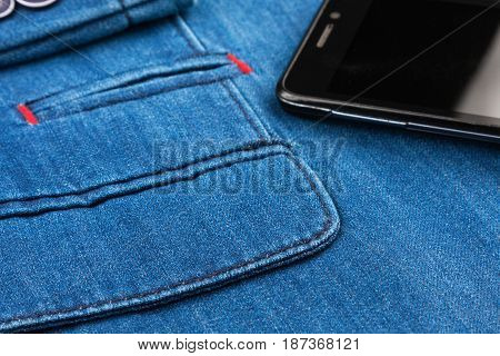 Close-up of pocket of denim jacket and phone. Fashion