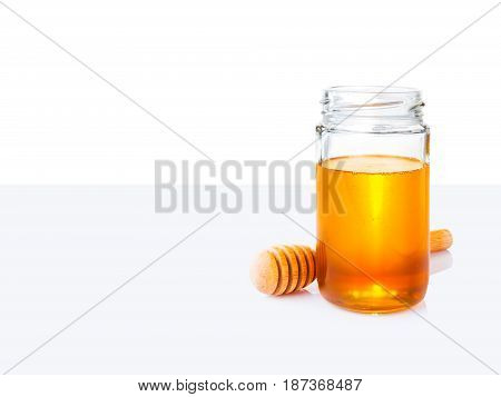 honey in glass jar and wooden honey dipper on white and light grey bacground with room for copy space