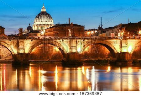 The Saint Angel bridge and St. Peter's Basilica in the background, Rome, Italy .