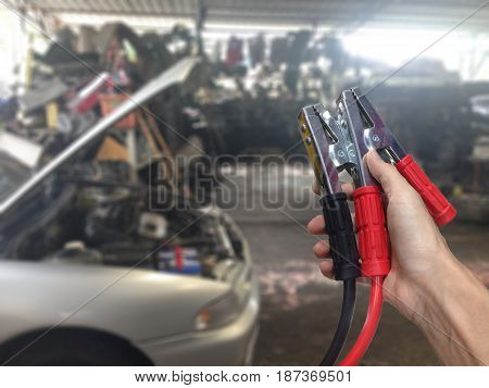 Hand holding Car battery charger over blurred car in garage background.