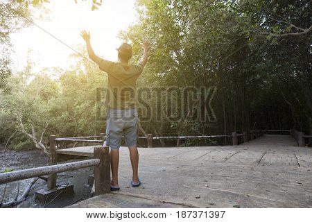 Alone man raised both hands up pray for blessings to god in forest