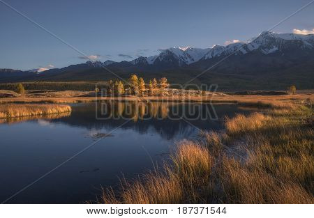 Mountain lake on a background of autumn landscape and snow capped mountains, Altai region, Siberia, Russia