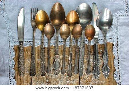 Metal spoons, forks, knives, on an old rustic table, like a frame used a tablecloth crocheted