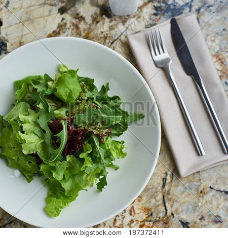 Lettuce salad served in white bowl with glass of white wine. Knife and fork lying on textile napkin on marble table. Top view or flat lay.