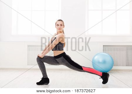Fitness woman warmup stretching training at white background indoors. Young slim girl makes aerobics exercise.