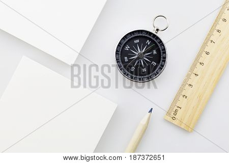 compass with blank white business paper rulerpencil on white backgroundBusiness direction concept
