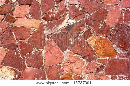 Stone masonry wall as background, stone  texture. Red shade of aging