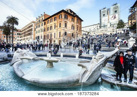ROME, ITALY. JANUARY 24, 2016: Spanish Square in Rome, Italy. Crowded with tourists and visitors. The Spanish Steps in Rome with fountain called Fontana della Barcaccia