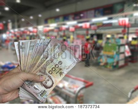 Hand holding trading and payments over blurred Cashier Supermarket background.