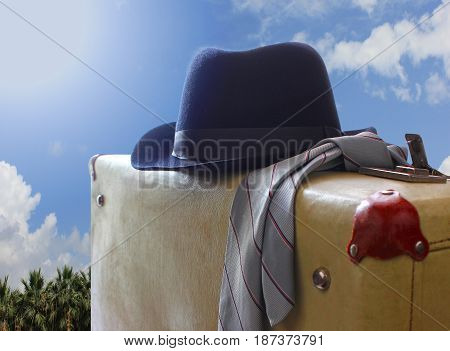 Tie Suitcase and hat, retro against a background of travel. Travel accessories clothing