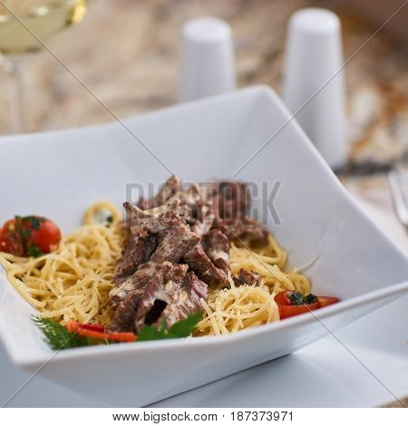 Beef stroganoff with spaghettini served in stylish square bowl on marble table