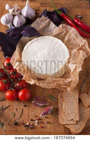 Cheese platter with fruits, homemade indian paneer cheese on wooden board with herbs, vertical