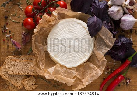 Cheese platter with fruits, homemade indian paneer cheese on wooden board with herbs, top view