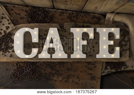 Illuminated Letters Spelling Cafe On Wooden Surface