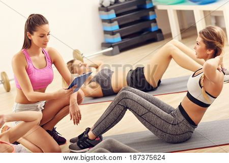Young women doing sit-ups in a gym