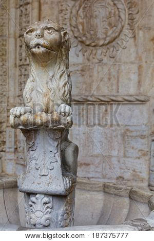 LISBON, PORTUGAL - MAY 11, 2017: Statue of marble lion in the cloister of Jeronimos Monastery. Since 1983, the monastery is listed as UNESCO World Heritage site