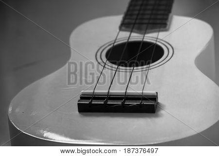 Close up of musical instrument ukulele guitar on gray tile floor. (Black and White filter effect)